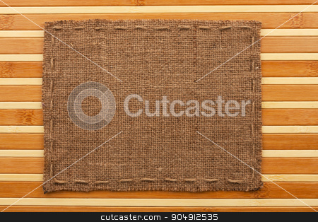 Frame of burlap, lies on a background of  bamboo mat stock photo, Frame of burlap, lies on a background of  bamboo mat, with place for your text by alekleks