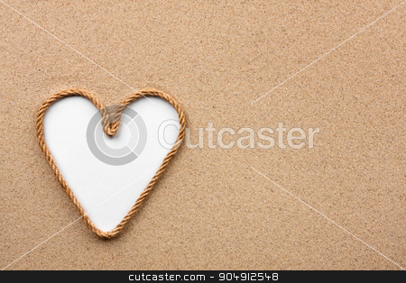 Heart made of rope with a white background on the sand stock photo, Heart made of rope with a white background on the sand, with place for your text by alekleks