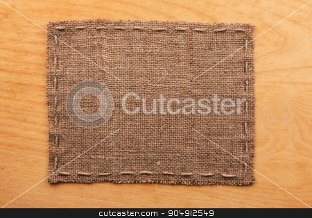Frame of burlap, lies on a background of wood stock photo, Frame of burlap, lies on a background of wood, with place for your text by alekleks