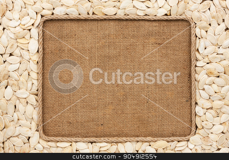Frame made of rope with pumpkin seeds on sackcloth stock photo, Frame made of rope with pumpkin seeds on sackcloth, with place for your creativity by alekleks