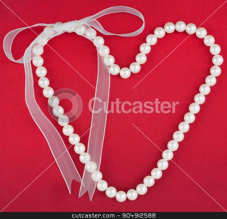 Symbolic heart of beads stock photo, Symbolic heart of beads, on a red fabric  by alekleks