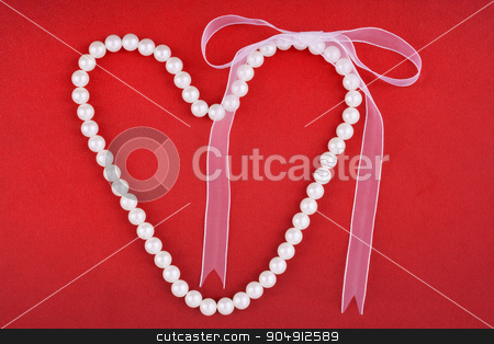 Symbolic heart of beads  with bow stock photo, Symbolic heart of beads  with bow, on a red fabric  by alekleks