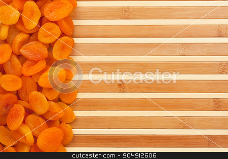 Dried apricots lying on a bamboo mat  stock photo, Dried apricots lying on a bamboo mat as background by alekleks