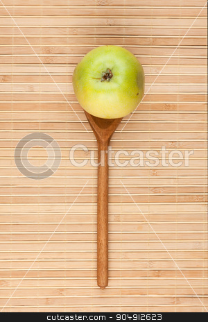 Spoon with green apple lying on the bamboo mat stock photo, Spoon with green apple lying on the bamboo mat, as background by alekleks
