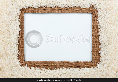 Frame made of burlap with the line and  rice  grain  lies on whi stock photo, Frame made of burlap with the line and  rice  grain  lies on white background, with place for your creativity by alekleks