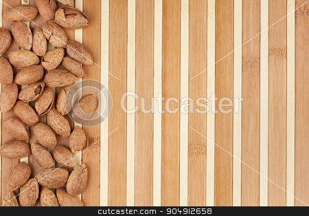 unpeeled almonds lying on a bamboo mat  stock photo, unpeeled almonds lying on a bamboo mat can be used as background by alekleks