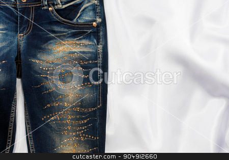 Trendy jeans with rhinestones lies on white silk stock photo, Trendy jeans with rhinestones lies on white silk, with space for your text by alekleks