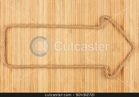Arrow made of rope  lies on a bamboo mat stock photo, Arrow made of rope  lies on a bamboo mat, can be used as background, texture by alekleks