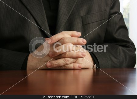 Businessman stock photo, Businessman at the office with his hands folded  by Mykola Komarovskyy
