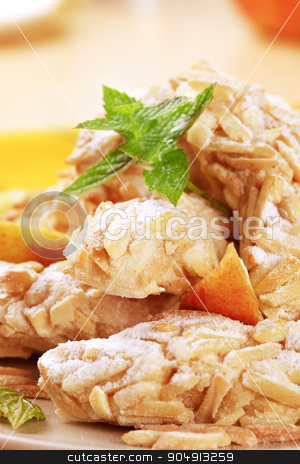 Almond cookies stock photo, Cookies rolled in chopped almonds and powdered sugar by Digifoodstock