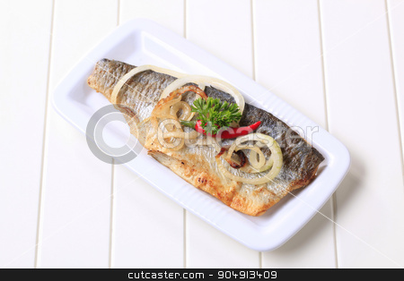 Pan fried trout fillet stock photo, Pan fried trout on a white platter by Digifoodstock