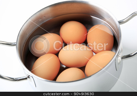Eggs in a saucepan stock photo, Brown eggs in water in a metal pot by Digifoodstock