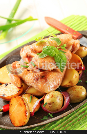Chicken wings and potatoes stock photo, Chicken wings and potatoes sprinkled with chives by Digifoodstock