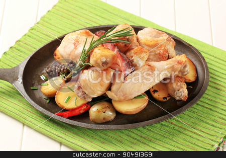 Rosemary chicken drumsticks and potatoes stock photo, Chicken drumsticks and potatoes on a cast iron skillet by Digifoodstock