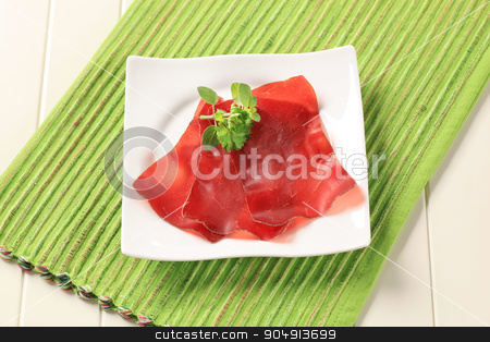 Dried meat stock photo, Thin slices of dried meat on a square plate by Digifoodstock