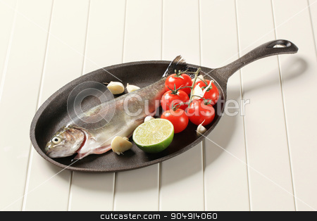 Fresh trout on a cast iron skillet stock photo, Fresh trout and vegetables on cast iron pan by Digifoodstock