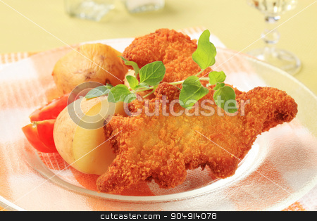 Fried breaded fish with potatoes stock photo, Fried dinosaur-shaped fish nuggets with new potatoes by Digifoodstock