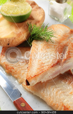 Skinless fish fillets with baked potato half stock photo, Pan fried fish fillets with roasted potato by Digifoodstock