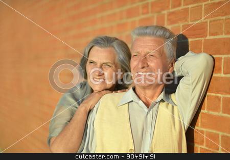 Mature couple near wall stock photo, Mature couple near wall on the street by Ruslan Huzau