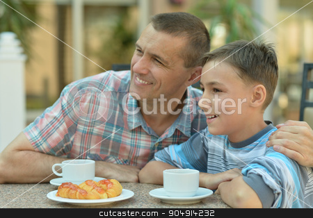 father with son at breakfast stock photo, Happy father with son at breakfast on the table by Ruslan Huzau