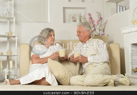 Elderly people with tea stock photo, Two elderly people sitting near couch with tea by Ruslan Huzau