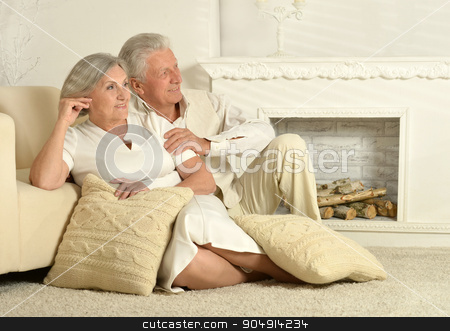 Elderly people sitting near  couch stock photo, Two elderly people sitting at home near couch by Ruslan Huzau