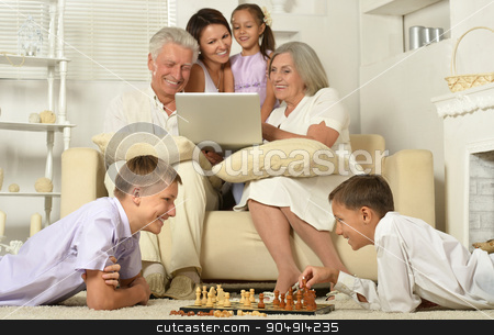 Happy family with kids with laptop stock photo, Happy family with kids on couch in living room with laptop,boys playing chess by Ruslan Huzau