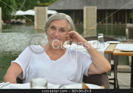 Older woman resting at tropical resort stock photo, Beautiful Older woman resting at tropical resort near pool by Ruslan Huzau