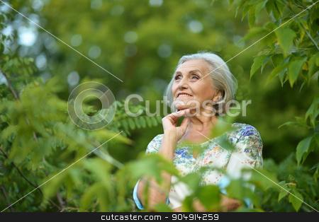 senior woman in summer park stock photo, Portrait of a senior woman in summer park by Ruslan Huzau