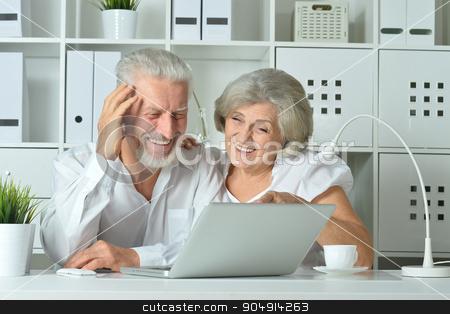 happy senior couple with laptop stock photo, happy senior couple with laptop  in office by Ruslan Huzau