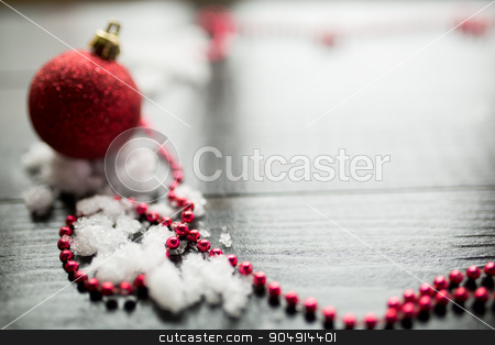 Red Christmas ball on snow on black wooden background stock photo, Christmas decoration closeup snowy background by sunapple