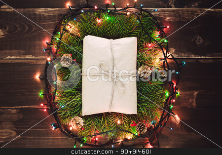 Christmas gift in the wreath stock photo, Christmas craft rustic gift closeup on the wooden table with garland lights by sunapple