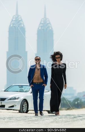 Couple on the background of skyscrapers stock photo, Lovable couple came out of the white car. A walk on a deserted beach in Dubai on the background of skyscrapers. The dark-haired woman in high heels with a fluffy head of hair in a black dress. A tall by bezikus