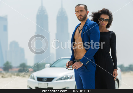 Couple on the background of skyscrapers stock photo, Pretty couple arrived in a white car to walk on a deserted beach on the background of skyscrapers in Dubai. The girl in a black dress. The man in the blue suit. OAE by bezikus