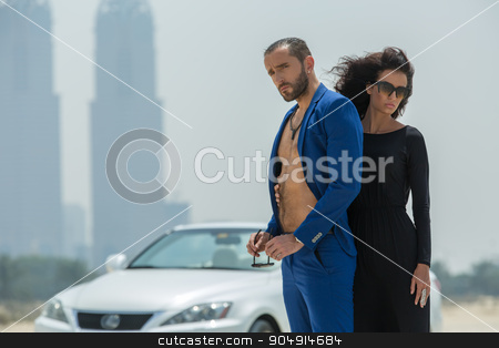 Couple on the background of skyscrapers stock photo, Tender couple arrived in a white car to walk on a deserted beach on the background of skyscrapers in Dubai. The girl in a black dress. The man in the blue suit. OAE by bezikus