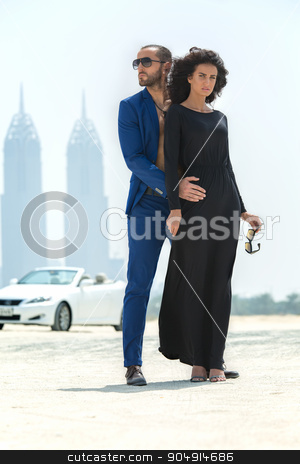 Couple on the background of skyscrapers stock photo, Young couple arrived in a white car to walk on a deserted beach in Dubai on the background of skyscrapers. The dark-haired girl in black dress took off her glasses and looking at the camera. The dark by bezikus