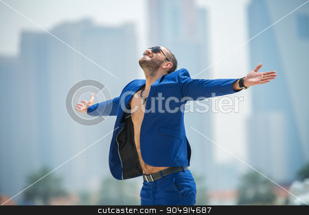 Man on the background of skyscrapers stock photo, Business man in a blue suit with a naked torso enjoys his arms in hand against the background of skyscrapers in Dubai. UAE. Horizontal photo by bezikus