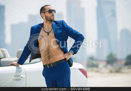 Man on the background of skyscrapers stock photo, Wealthy man arrived in a white car to walk on a deserted beach on the background of skyscrapers in Dubai. He wore a blue suit and naked torso. OAE by bezikus