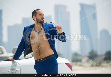 Man on the background of skyscrapers stock photo, Rich man arrived in a white car to walk on a deserted beach on the background of skyscrapers in Dubai. He wore a blue suit and naked torso. OAE by bezikus