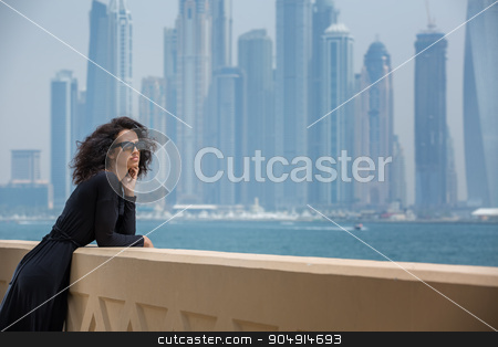 Woman on the background of skyscrapers stock photo, Refined dark-haired girl in black dress on the background of skyscrapers in Dubai. Admiring the sea. UAE. Horizontal photo by bezikus