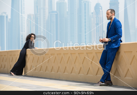 Couple on the background of skyscrapers stock photo, Elegant couple on the terrace with views of the skyscrapers in Dubai. The man in the blue suit. The dark-haired girl in a long black dress. UAE by bezikus