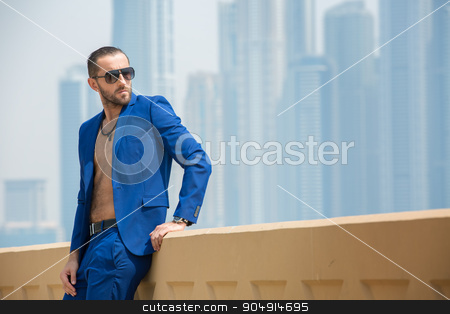 Man on the background of skyscrapers stock photo, Elegant man in a blue suit with a naked torso resting on the terrace in the background nebostrebov Dubai. UAE. Horizontal photo by bezikus