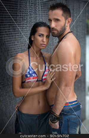 Couple in the shower stock photo, Daring couple relaxing in the shower wearing jeans outdoors. The dark-haired girl in a bathing suit. Tropics. Vertical photo by bezikus