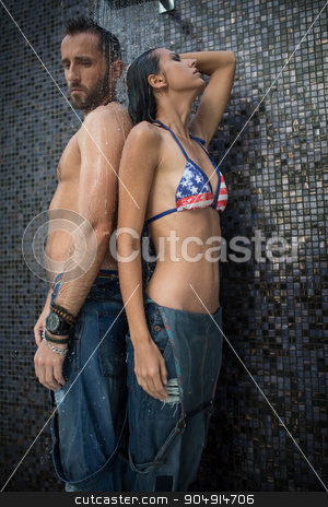 Couple in the shower stock photo, Slim tanned couple in jeans basking under the outdoor shower. Girl in swimsuit. Tropics. Vertical photo by bezikus