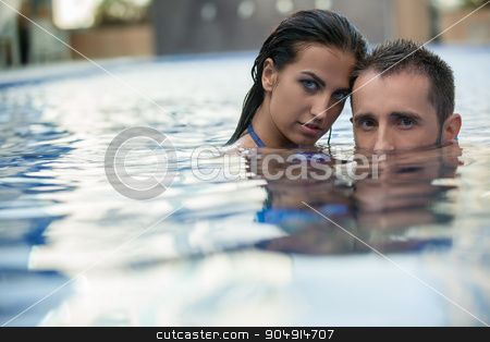Couple in the pool stock photo, Sweet young couple relaxing in the pool. The dark-haired woman leaned her head to the guy. He lowered his face half-submerged. Tropics by bezikus