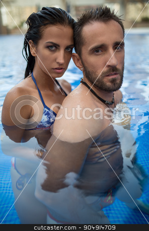 Couple in the pool stock photo, A loving couple basking in the crystal clear outdoor swimming pool. Girl in swimsuit. Tropics. Vertical photo by bezikus