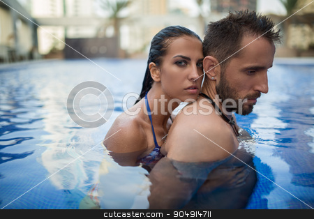 Couple in the pool stock photo, Cute tanned couple basking in the crystal clear outdoor swimming pool. Girl in swimsuit. Tropics. Horizontal photo by bezikus