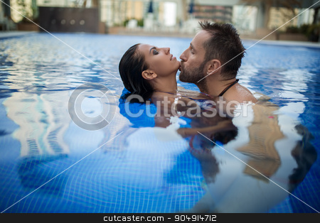 Couple in the pool stock photo, Charming tanned couple relaxing in the pool. Man with beard kisses the dark-haired girl in the neck. Tropics. Horizontal photo by bezikus