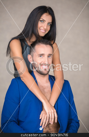 Young couple in the studio stock photo, Attractive couple in embrace on a brown background. The slender blue-eyed girl with long dark hair in a gray-black dress hugs the neck man in a blue suit with a beard. Vertical photo by bezikus