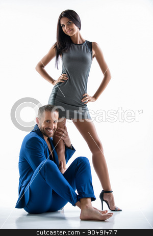 Young couple in the studio stock photo, Positive couple in the studio on a white background. Leggy girl with dark hair standing in a short dress. A man with a beard wearing a blue suit sitting on the floor.She hugs her leg by bezikus